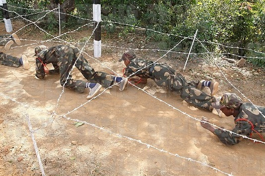 Commando obstacles training ; cadets crawling under the barbed wire ; Military school ; Amboli ; district Sindhudurga ; Maharashtra ; India MR 703M